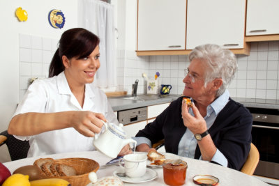 caregiver and elderly woman eating together